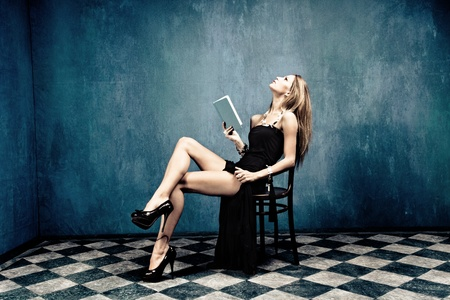 sensual blond in black dress and high heels sit on chair holding a book in empty room
