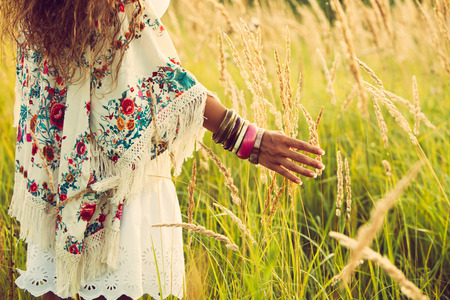Photo pour woman wearing boho style clothes touching grass, hand with lot of braceletes, summer day in the field, retro colors - image libre de droit