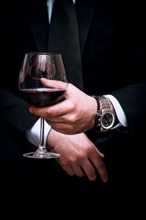Photo pour adult elegant man hold glass of red wine, close up, indoor shot, selective focus - image libre de droit