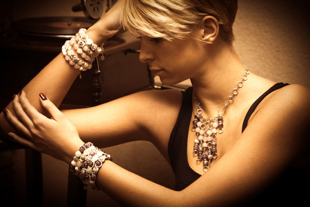 Foto de short hair blond elegant young woman portrait wearing jewelry, necklace and lot of bracelets, indoor shot, side view - Imagen libre de derechos