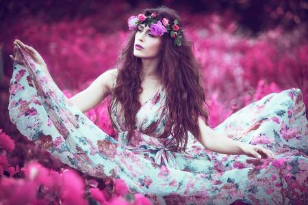 Photo pour beautiful playful fairy  woman in fluttering floral dress in unreal pink field - image libre de droit