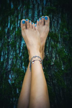 Foto de barefoot woman feet with ankle bracelets lean on tree with moss, natural light, selective focus - Imagen libre de derechos