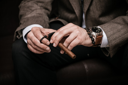 Photo for elegant man wearing suit and white shirt cut Cuban cigar indoor shot, closeup, selective focus - Royalty Free Image