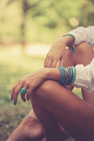 Foto de turquoise ring and bracelets on woman hand sit barefoot on grass in wood, closeup,  warm summer day, selective focus, - Imagen libre de derechos