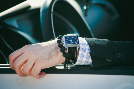 Foto de man hand in elegant suit with watch and bracelet lean on car window, closeup natural light, shallow depth of field - Imagen libre de derechos