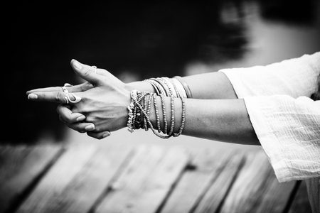 Foto de woman hands in yoga symbolic gesture mudra wearing lot of bracelets and rings outdoor closeup by the lake summer day bw - Imagen libre de derechos