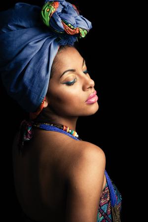 Foto de African black young woman beauty portrait with turban headscarf and traditional colorful clothes studio shot - Imagen libre de derechos