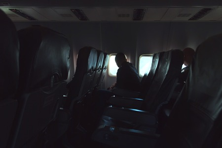 Foto de The passenger looks out the window, bright light in the Windows of the aircraft. photo in low key - Imagen libre de derechos