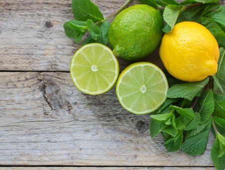 Photo pour Juicy ripe citrus on an old wooden table - lime, lemon and mint - image libre de droit