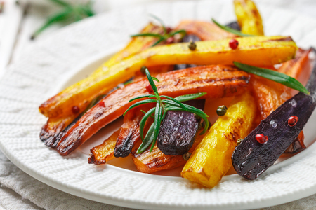 Photo for Roasted carrots with rosemary, coarse sea salt and pepper. Colorful vegetables and spices. Vegetarian dish. Selective focus - Royalty Free Image