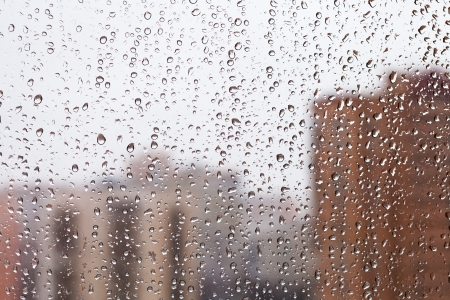 raindrops on home glass window with city buildings background