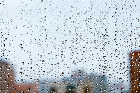raindrops on glass window with blue evening city background