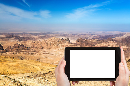 travel concept - tourist photograph mountain landscape of Jordan near Petra on tablet pc with cut out screen with blank place for advertising