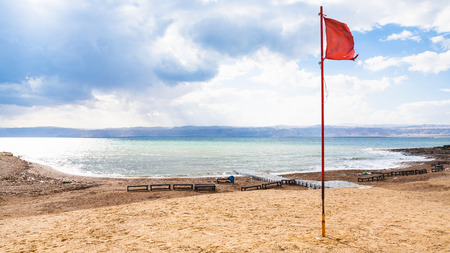 Travel to Middle East country Kingdom of Jordan - red flag on beach in cold day on Dead Sea in winter season