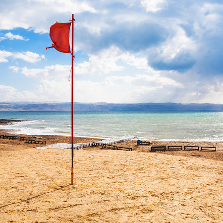Travel to Middle East country Kingdom of Jordan - red flag on beach of Dead Sea in winter season