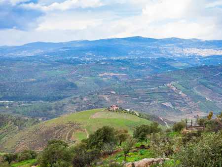 Travel to Middle East country Kingdom of Jordan - green hills in valley Zarga River in Jordan in winter