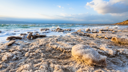 Travel to Middle East country Kingdom of Jordan - piece of salt close up on shore of Dead Sea on winter sunset