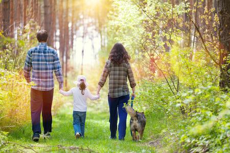 Foto de Family with dog walking in the forest back to camera - Imagen libre de derechos