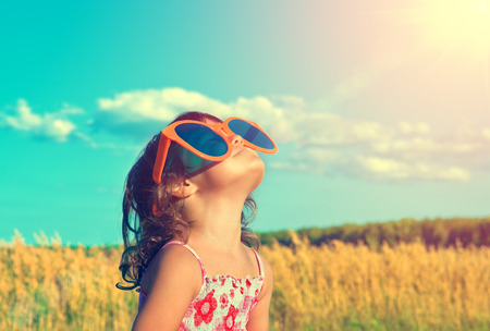 Photo pour Happy little girl with big sunglasses looking at the sun - image libre de droit