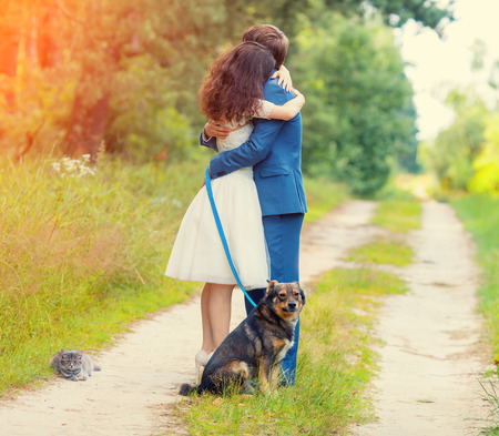 Young couple hugging in the forest. Dog and cat sitting near the couple.