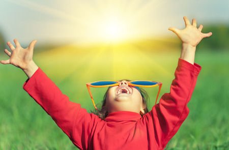 Photo pour Happy little girl wearing big sunglasses with hands up enjoying sun in the field - image libre de droit