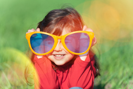 Photo pour Happy smiling little girl wearing big sunglasses in the field - image libre de droit