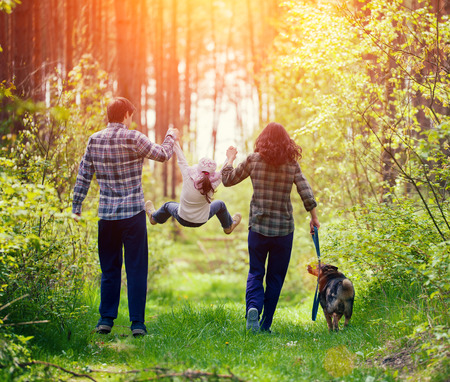 Foto de Happy family walking with dog in the forest - Imagen libre de derechos
