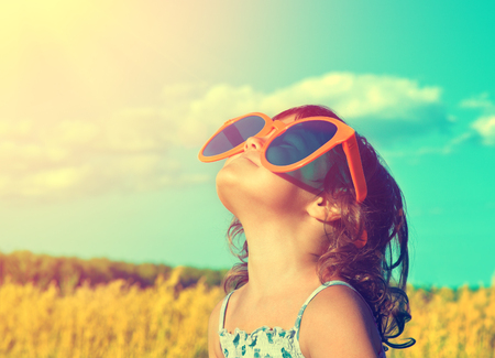 Photo pour Happy little girl with big sunglasses looking at the sun in the wheat field in summer - image libre de droit