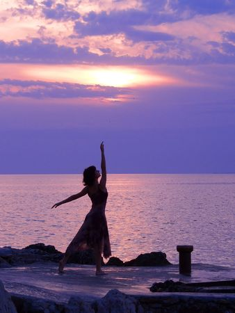 Photo for Young woman standing at ballerina pose, sunset at the background - Royalty Free Image