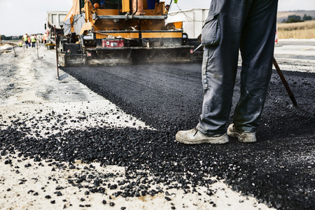 Photo for Worker operating asphalt paver machine during road construction and repairing works - Royalty Free Image