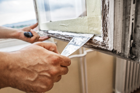 Foto de Repairing a window frame -Man using scraper and putty for renovation old windows - Imagen libre de derechos