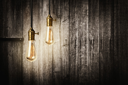 Foto de Edison retro light bulbs on wooden background - Imagen libre de derechos