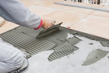 Foto de Home improvement, renovation - handyman laying tile, trowel with mortar - Imagen libre de derechos