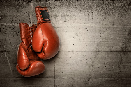 Foto de Boxing gloves hanging on concrete wall -including clipping path - Imagen libre de derechos
