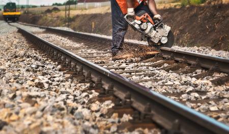 Photo pour Reconstruction of the railway -Worker on the railway cuts rail with a machine - image libre de droit
