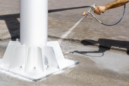 Foto de Worker uses an airless spray to paint the metal construction - Imagen libre de derechos