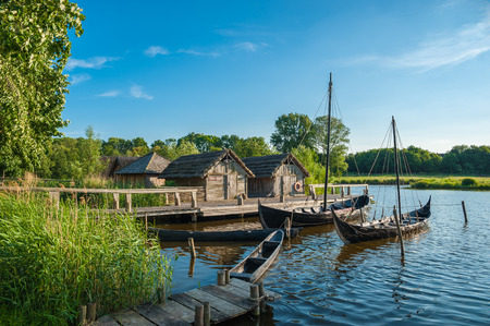 Photo pour Buildings of a slavic village with a viking ship and a slavic merchant-ship in the museum Wallmuseum in Oldenburg in Holstein - image libre de droit
