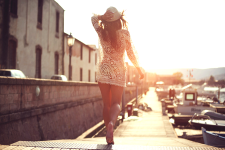 Photo for Young woman in hat and cute summer dress standing on the pier with peaceful town scenery, looking at sunset. - Royalty Free Image