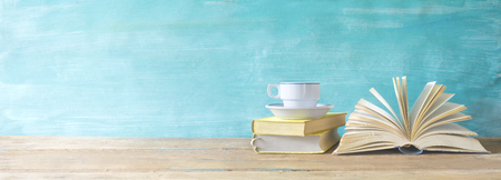 Photo pour opened book, cup of coffee on grungy background, panoramic, copy space - image libre de droit