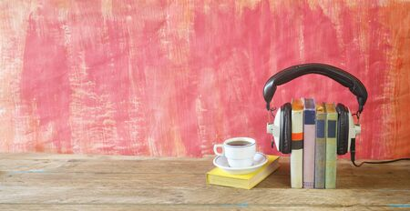 Foto de audio book concept with book, headphones and cup of coffee, panorama format on grungy background, good copy space - Imagen libre de derechos