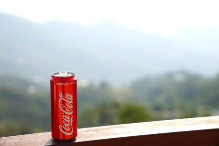Foto de Chiang rai, THAILAND, Febuary 18, 2018 : Classic red Coca-Cola can with background of mountain layers. - Imagen libre de derechos