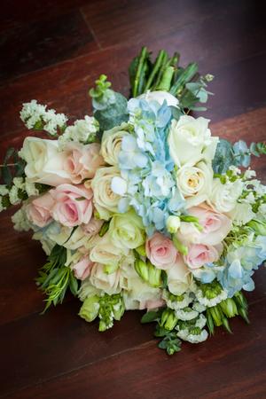 Foto de Wedding bouquet lying on wooden floor in bride room. - Imagen libre de derechos