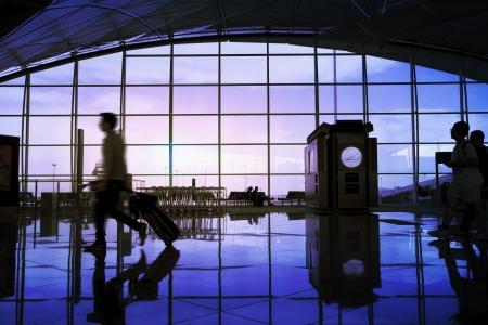 Airport terminal hall, walking travelers