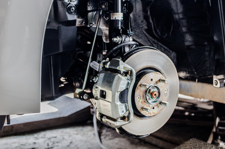 Foto de Front disc brake on car in process of new tire replacement. The rim is removed showing the front rotor and caliper - Imagen libre de derechos