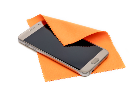 Photo pour Smartphone cleaning dirty screen with orange fabric,isolated on white background - image libre de droit