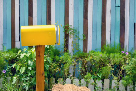 Foto de yellow vintage mailbox with wooden wall in garden - Imagen libre de derechos