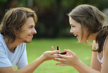 Candid proposal outdoor in the park, attractive couple