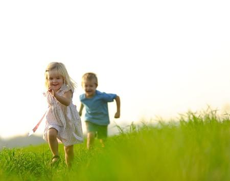 Foto de Young girl runs through a field, happy and having fun. - Imagen libre de derechos