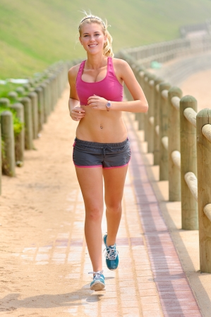 Foto de Fit young woman jogging on a pathway - Imagen libre de derechos