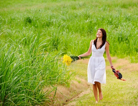 Adorable girl walks barefoot in field with flowers in hand